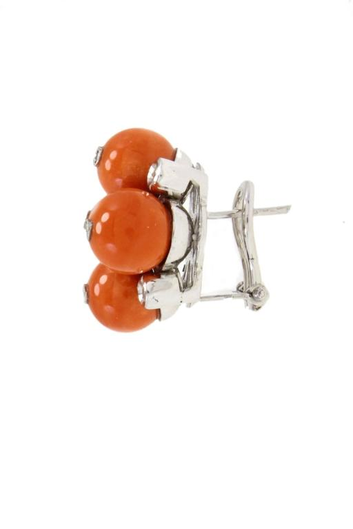 Spheres of coral composed these lovely earrings in 14kt white gold with shiny diamonds.  diamonds 0.27kt coral 6.72gr tot weight 24.6gr r.f. uuig