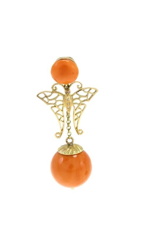 A little taste of spring with these delightful coral earrings. Carved in 14Kt gold there is a butterfly that links to the coral sphere on the bottom, and it is embellished with little diamonds on the body. Diamonds (0.04Kt) Coral (9.50gr)  tot