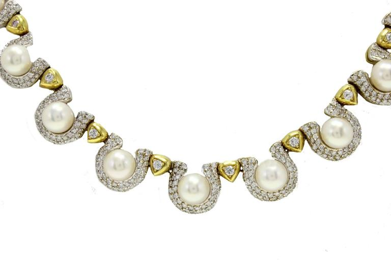 Elegant necklace in 18kt white and yellow gold composed of pearls surrounded by diamonds linked each other by a yellow gold drop with a central diamond. diamonds 11.50 kt pearls 7.80gr tot weight 103.3 gr r.f. fraaa For any enquires, please contact