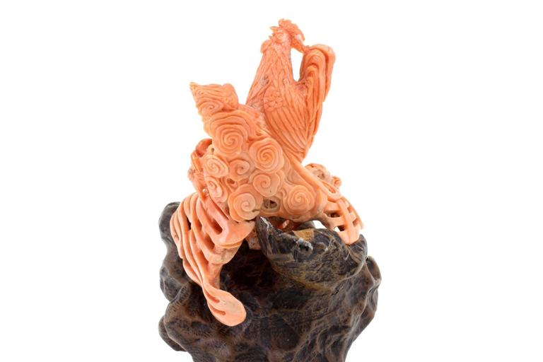 This carved coral sculpture represents a chicken family composed of a rooster, a hen and two chicks. On the bottom there is a wood movable piece.  coral 185gr r.f. gaeaa