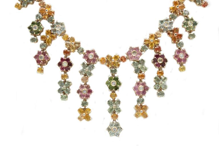 Shiny and springy necklace in 14kt yellow gold composed of flowers shaped multi-colored sapphires with a central diamonds each. fresh to wear!  diamond 1.60kt sapphires 61.55kt tot weight 60.8gr r.f.  gfoaf