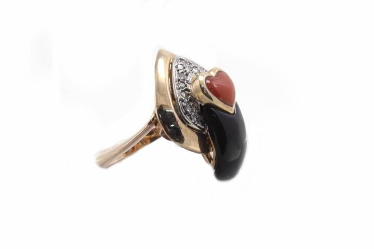 A shiny heart shaped coral surrounded of a spade shape diamond and onyx, all mounted in 14Kt yellow gold. Ring Size: US 7.5 - ITA 16 - French 56 - UK P  Tot weight 10gr Diamonds 0.26 Kt Coral 0.15 gr Onyx 0.75 gr  Rf.guca