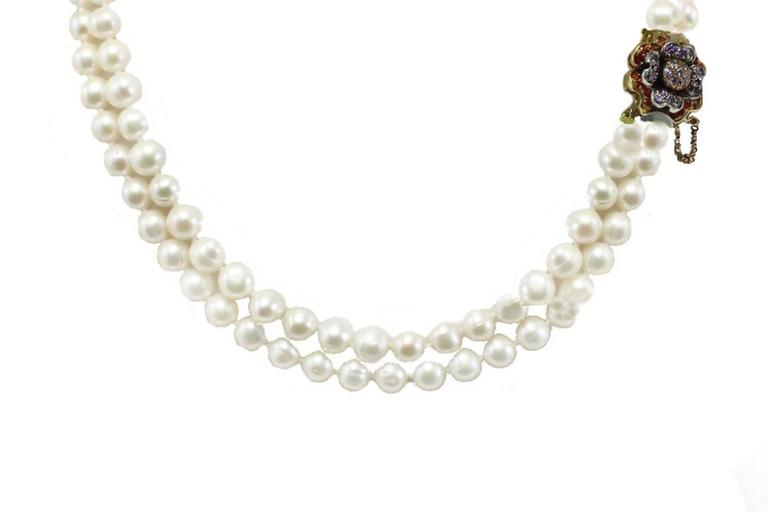 Beaded necklace with a shiny flower shaped clasp in 9kt yellow and rose gold and silver covered in coloured gemstones.  pearls 7mm/ 0.27inch tot weight 60.3gr r.f.   car