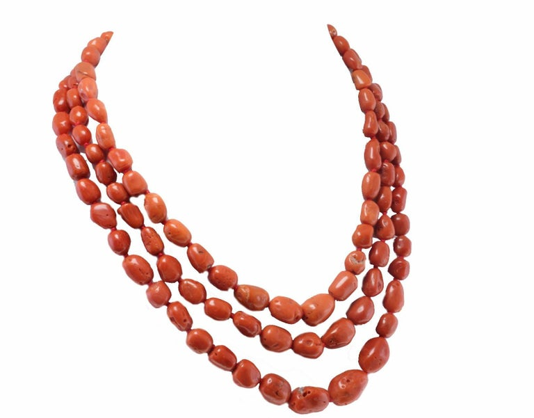 Fascinating 3 strands barrel shaped coral necklace with a clasp composed of diamonds encrusted on a base in 14 white gold and silver with 3 central garnet. Diamonds 0.09 ct Garnet 2.8 Coral 146.7 g  Rf. faca