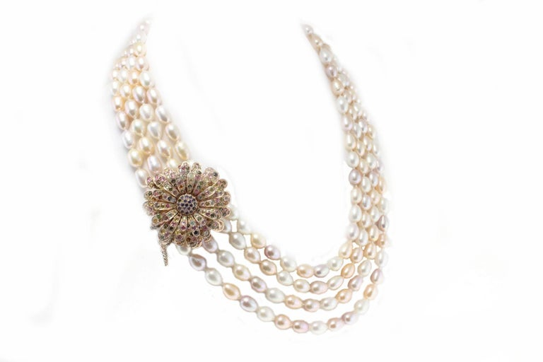 Fascinating 4 strands beaded necklace with a clasp composed of tourmalines and iolite encrusted on a base in 9 K rose gold and silver Tot weight 262.9 g Tourmaline and iolite21.28 ct Pearls 216.50 g  Rf. ucce