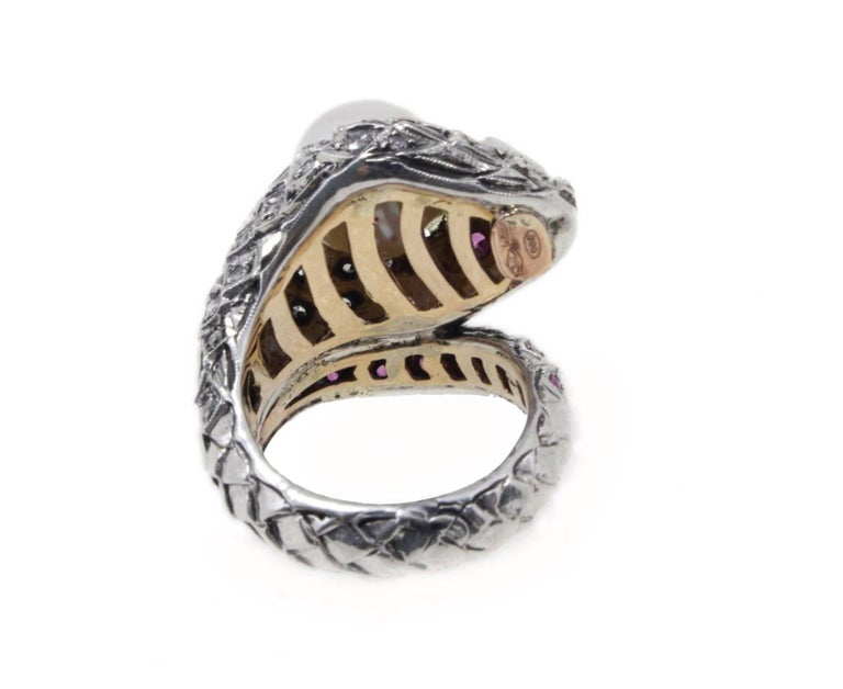 Sparkling and graceful cocktail and fashion ring snake shape. All is mounted in 9Kt rose gold and silver. The body is adorned of diamonds and rubies , in the middle of the forehead a single fancy diamond and on top of the head a pearl. Ring Size: