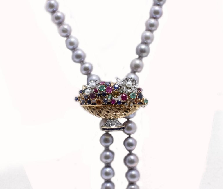 Charming beaded necklace  of a single strand of grey pearl and a clasp composed of emeralds, blue sapphires, rubies and diamonds. All is mounted in 14 Kt white gold and 14 Kt rose gold. Tot weight 88.6 g Diamonds 0.43 ct Blue Sapphire,