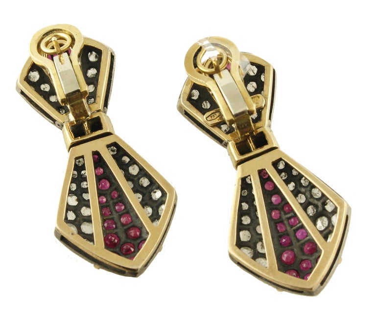 Fascinating clip earrings in 18 kt yellow gold and silver, 4 cm long, all studded with 2.38 ct diamonds, rubies and 7 ct emeralds. Total weight g 21.31 Diamonds ct 2.38 Rubies / Emeralds ct 7 Total weight g 21.31 / length 4 cm RF + fcof