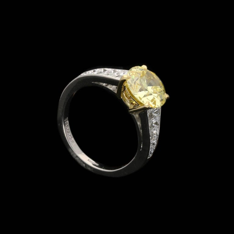 Contemporary 2.41 Carat Fancy Intense Yellow Diamond Ring with Tapering French-Cut Diamond For Sale