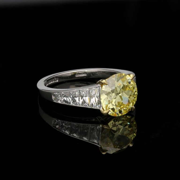 A stunning yellow and white diamond ring by Hancocks, the ring centred on an old European brilliant cut diamond weighing 2.41 carats and of Fancy Intense Yellow colour and VS1 clarity four claw set in 18 carat yellow gold with yellow diamond detail