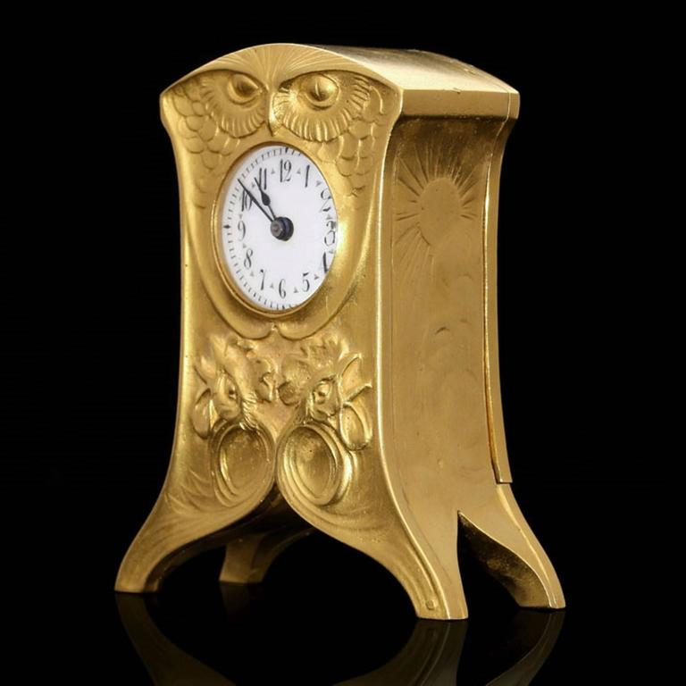 The clock in satin-finish 18ct yellow gold with detailed repoussé and chasing work in the Art Nouveau style depicting contrasting motifs all symbolic of day or night. The front with an owls head forming the top beneath which the dial is set, the