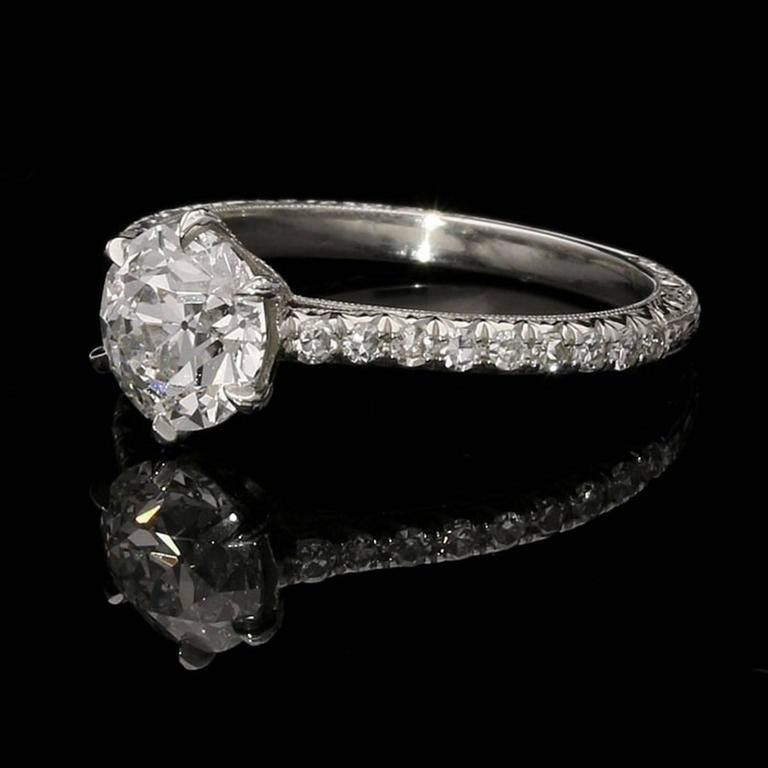 The solitaire style ring with a beautiful old European brilliant cut diamond weighing 1.33ct and of F colour and VVS2 clarity claw set in an ornate finely crafted and hand engraved platinum mount with single-cut diamonds set in the shoulders.