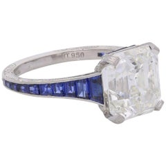 5.03 Carat Asscher Cut Diamond Ring with Elegant Tapering Calibre Set Sapphire