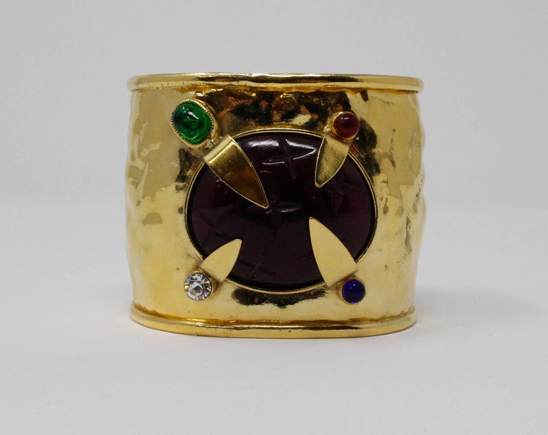 Daum by Hilton McConnico Cuff Bracelet. C. 1960. The cuff is two inches wide, features multicolored faux stones. The center stone is an amethyst while the surrounding stones are emerald, diamond, ruby and sapphire. The cuff is in wonderful