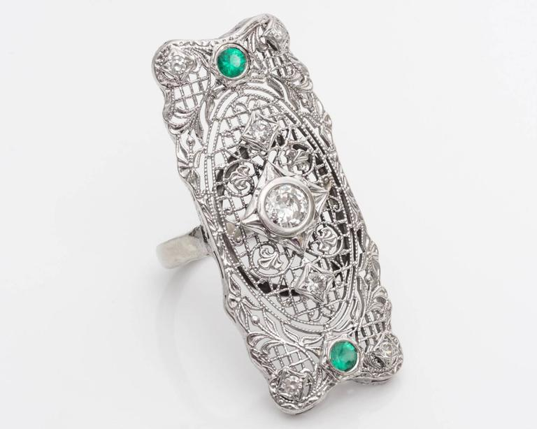 14 Karat White Gold Filigree Shield Ring Full of Intense and Delicate Filigree Scroll Design  Features Diamonds and Emeralds Fits Ring Size 7, Resizable   Center Diamond Details: Transitional Cut round, Weighs 0.33 Carats, G Color, SI1 Clarity,
