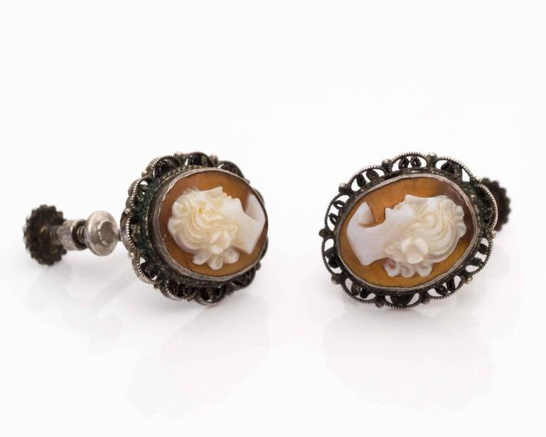 These unique cameo earrings from 1870s are exceptionally beautiful! The intricate hand-carved cameo relief is lovely and elegant. The relief displays a visage of a woman in white with the classic pinkish shell backdrop. The detailed etchings show