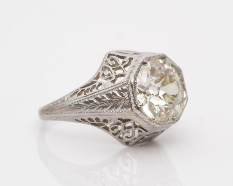 1920s Art Deco GIA 1.45 Carat Old European Diamond Platinum Engagement Ring. Set in a Stunning Milgrain Bezel Frame surrounded by Heavy Intricate Filigree and Cutouts, visible on all sides. The shoulders of the ring feature leaf designs etched into