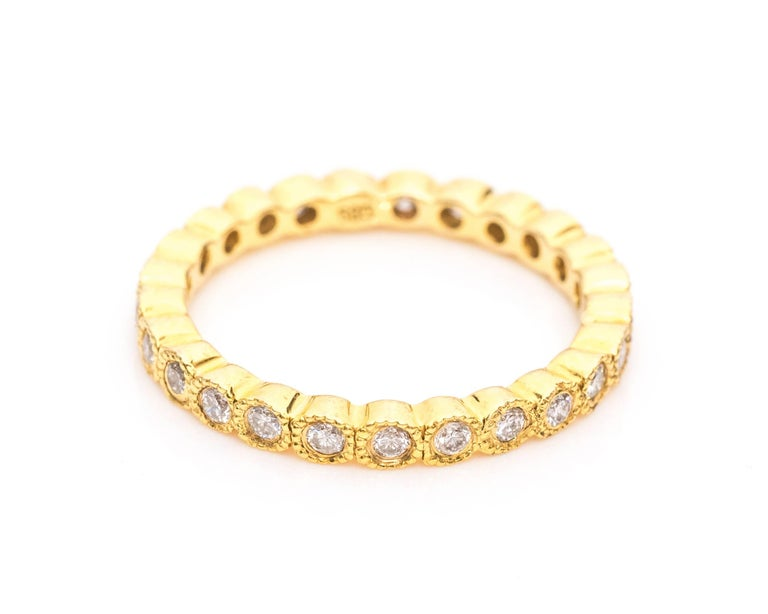 Absolutely beautiful 14 karat yellow gold eternity diamond band ring.  Each diamond is set in a bezel frame of 14 karat yellow gold with a milgrain pattern along the border. The diamonds surround the entire ring making it an eternity band.   This