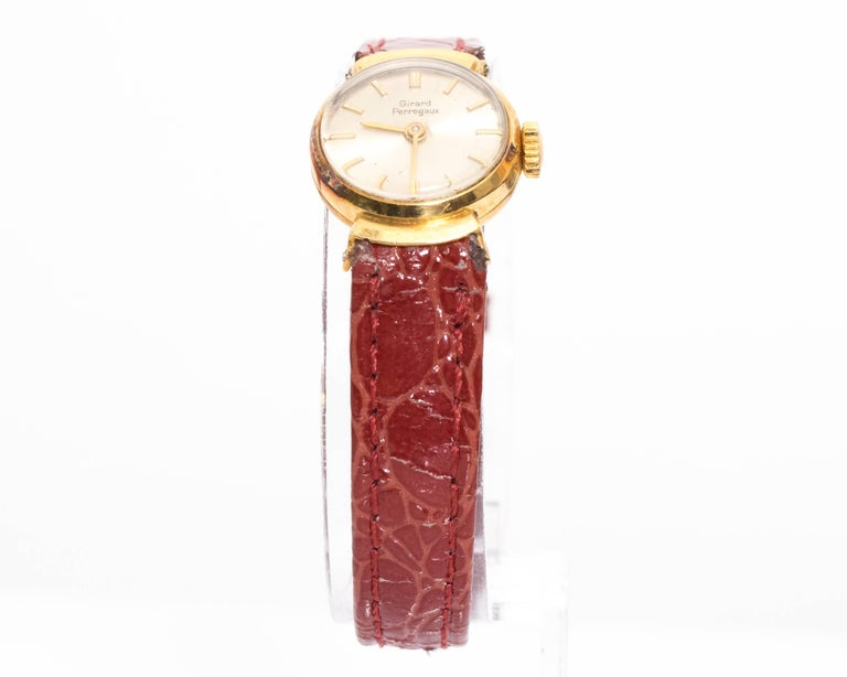 1950s Girard Perregaux Ladies Wristwatch Yellow Gold Made in Switzerland Winding movement watch Patina on Metal, common due to age of watch. Hints of rainbow color on case.  Fits 7.5 inch wrist Case Size is 16 millimeter  Band is an after market red