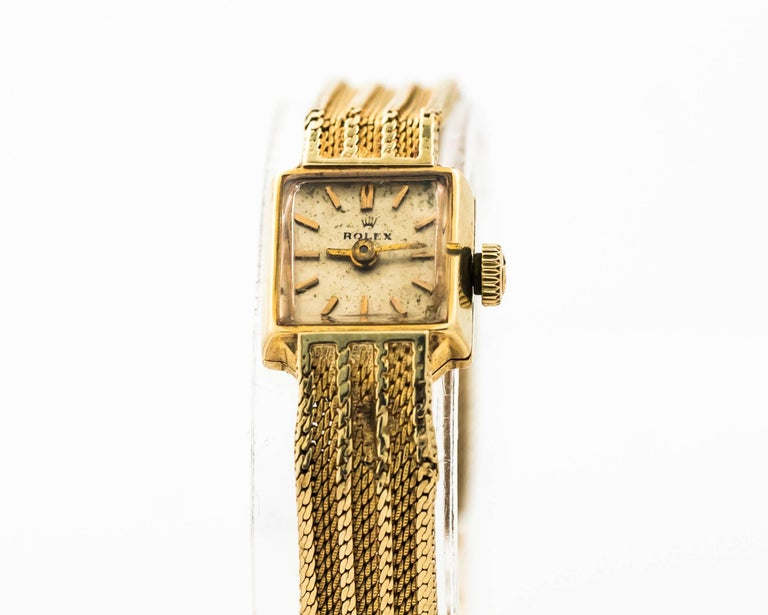 1950s Rolex Wristwatch for Ladies 14 Karat Yellow Gold  Manual Wind Crown on this watch is Omega Brand. The watch was purchased in a boutique where Omega watches were sold as well.   Made in France (hallmarked on the clasp) Band and Dial has some