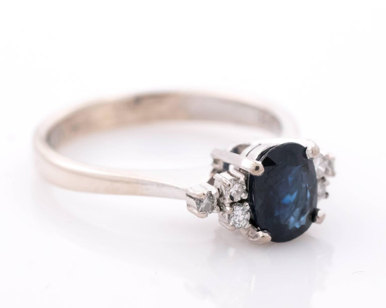 This 1950s retro vintage Blue Sapphire and accent Diamond Ring features a Cathedral Setting with Gallery. The 1 Carat Oval Blue Sapphire center stone is flanked by 6 round brilliant Diamonds, 3 on each side - perfect add of sparkle to the