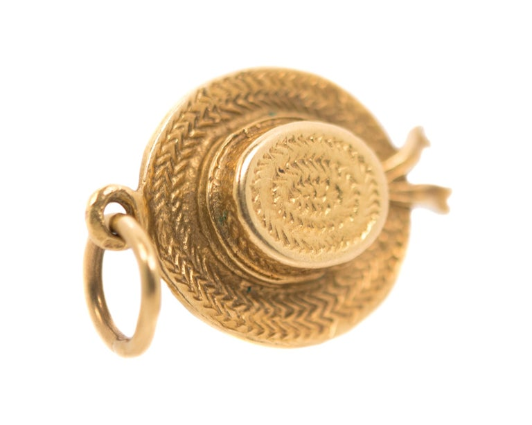 1970s Hat Pendant - 14 Karat Yellow Gold  Features:  14 Karat Yellow Gold Woven straw-textured gold wrap around Gold Ribbon with Bow  fixed round bail 24 millimeters long x 16 millimeters wide  Pendant Details: Metal: 14 Karat Yellow Gold Weight: