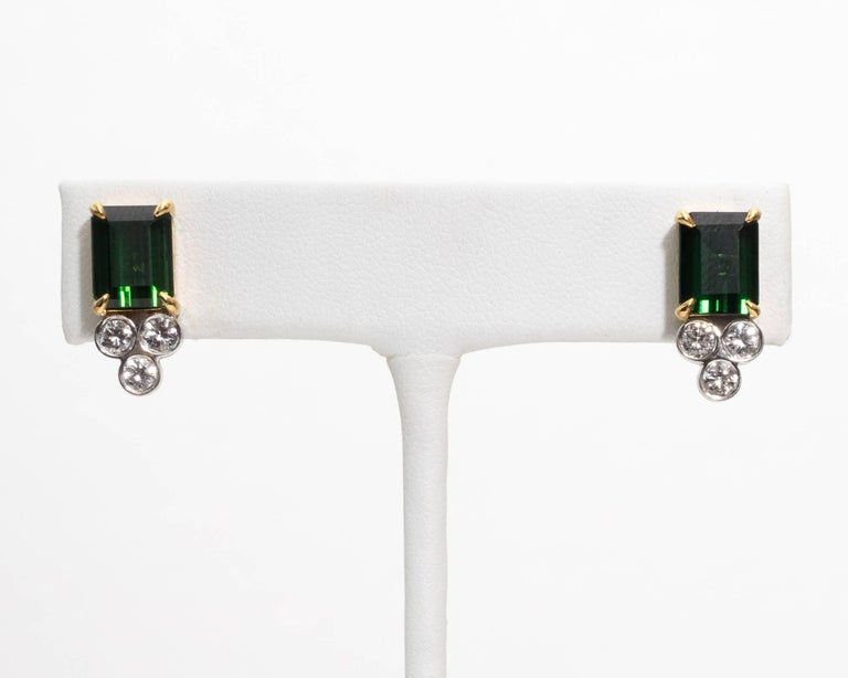 Brighten any day with this timeless pair of elegant green tourmaline and diamond stud earrings! Crafted in 14 Karat Yellow Gold Features Two Emerald Cut Green Tourmaline, approximately 4.95 carats total weight that are a gorgeous medium dark green
