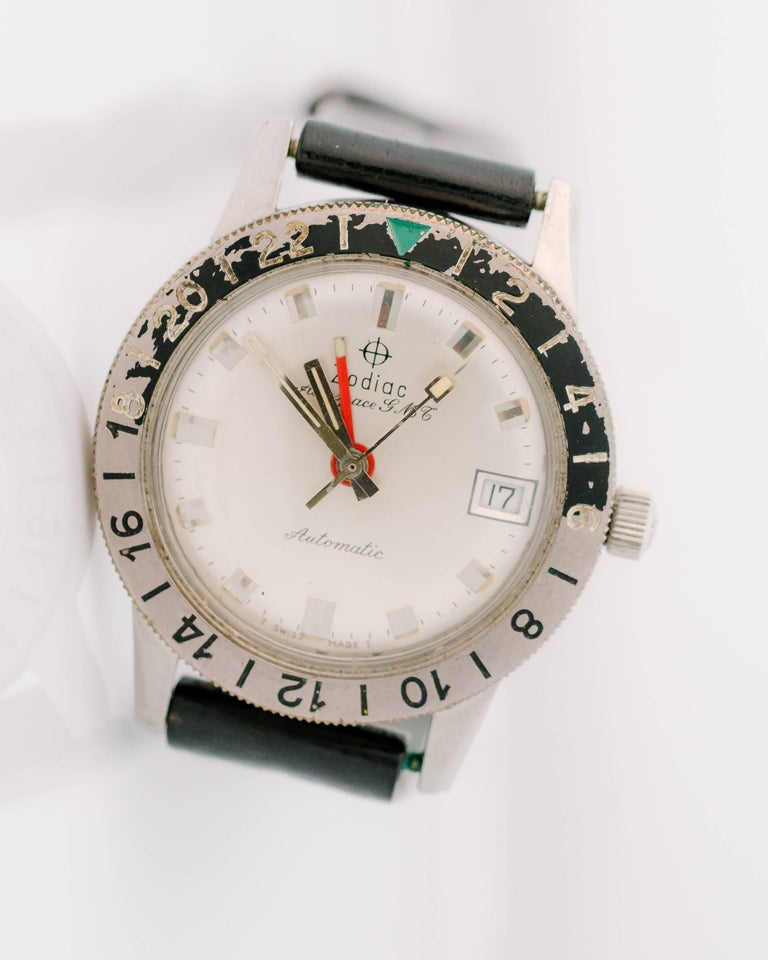This 1950s Retro Zodiac Aerospace GMT Automatic Stainless Steel unisex wrist watch was designed with the world traveler in mind! The 24 hour black and grey rotating bezel has a green triangle 24 hour index. This allows the wearer to adjust for