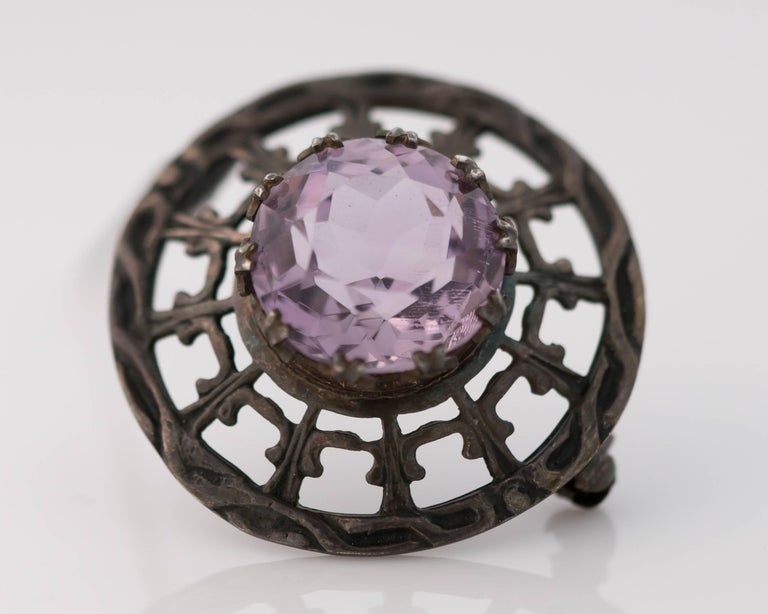 This 1910s Edwardian Era Brooch boasts a 10 Carat Old Miner Cut Amethyst set in Sterling Silver. This stunning 15 millimeter Amethyst is set with 10 talon double prongs for extra security. The classically patterned sterling silver has achieved a