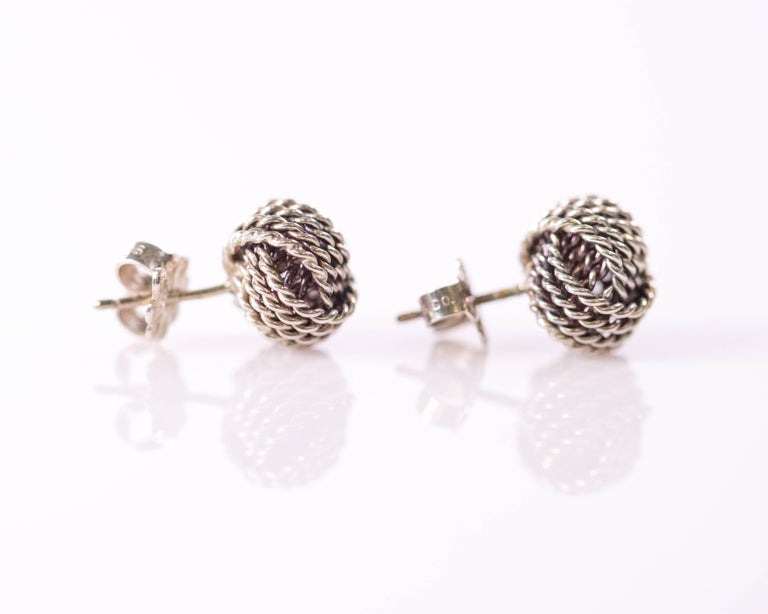 These Tiffany and Co. Sterling Silver Twist Knot Earrings are a Vintage Classic. They measure 8 millimeters across and feature 3 overlapping bundles of 4-strand twisted cable sections which combine to form a single knot.  They have push back posts