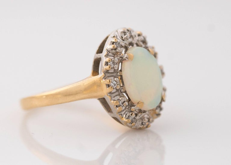 1960s Retro Opal with Diamond Halo, 14 Karat Yellow Gold Ring. Features a Natural Opal Cabochon with green and orange color play. The prong set Oval Opal measures 9 millimeters long by 7.1 millimeters wide. It is surrounded by a 0.10 carat total