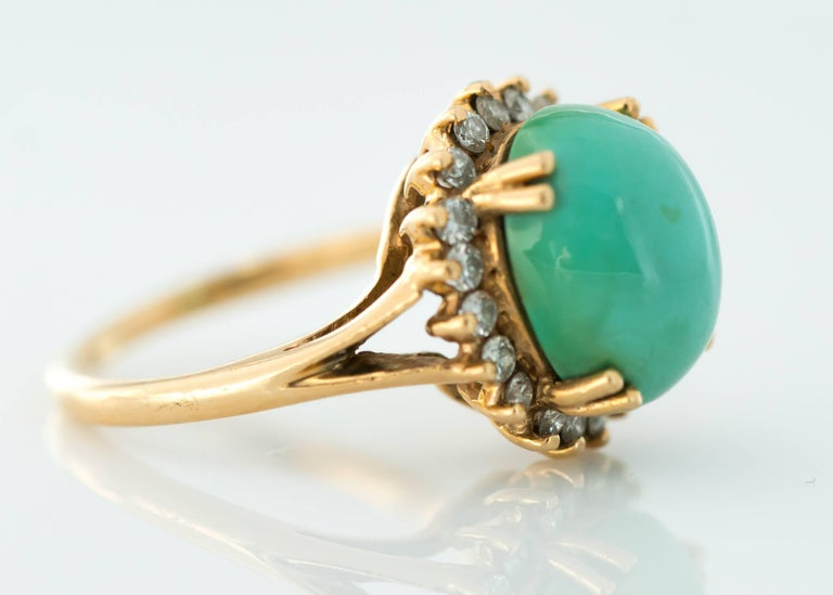 Tiffany and Co. Persian Turquoise Cabochon, Diamond Halo and 14 Karat Yellow Gold Ring  Features a 12 millimeter by 10 millimeter Persian Turquoise Cabochon securely set with 4 double prongs. A Diamond Halo frames the stunning center stone.