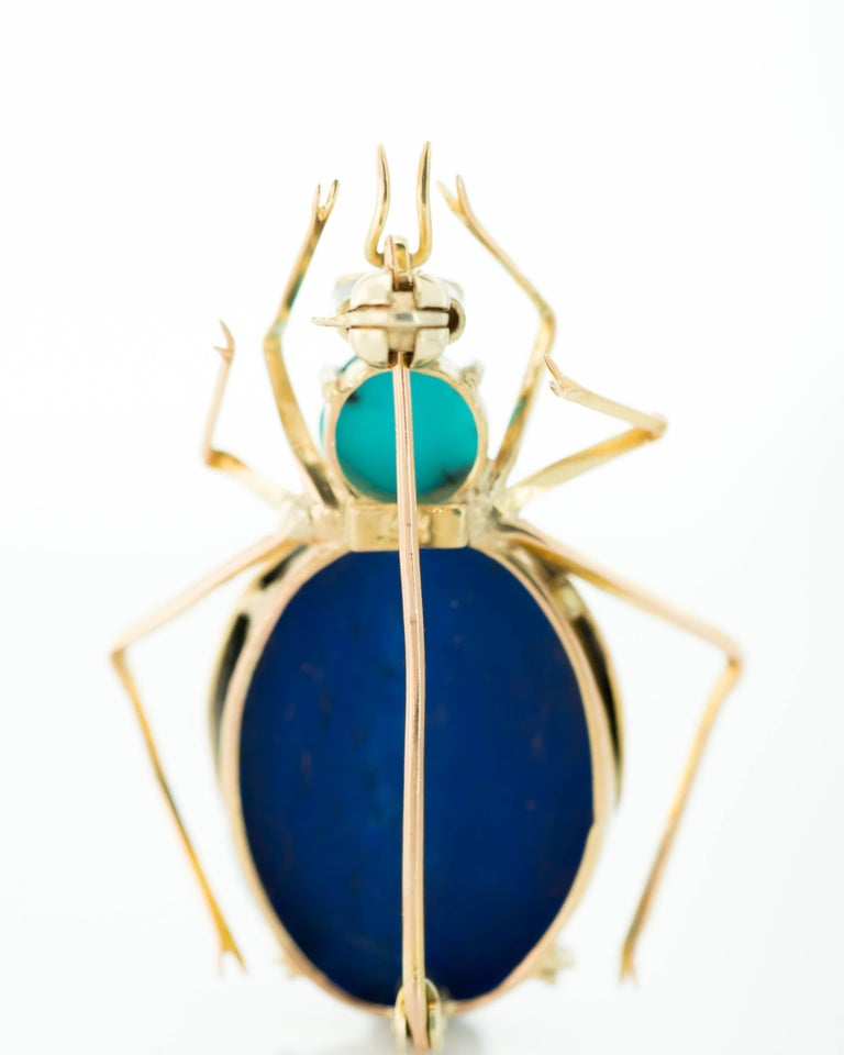 1950s Insect Brooch - Lapis Lazuli, Turquoise, Ruby, 14 Karat Yellow Gold  Features an Oval Lapis Lazuli Cabochon Body, Turquoise Head and 2 Ruby Eyes. 14 Karat Yellow Gold frames the body and forms the 2 Wings, 6 Legs and 2 Pincers. The deep blue