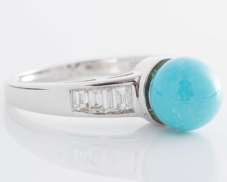 Vintage 1970s Ring - 18K White Gold, Turquoise, Diamonds  Features an 8 millimeter Turquoise cabochon and 8 Diamond Baguettes. The gorgeous blue Turquoise is center set. It is flanked by 4 Diamond baguettes on each side. The ring shank is crafted