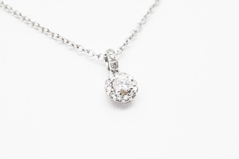 Ferrucci white diamond pendant embraced by diamond halo, the classic of fine jewelry for a fine elegant neck, Made in Italy Entirely made in 18k white gold  Diamond total carat weight 0.26