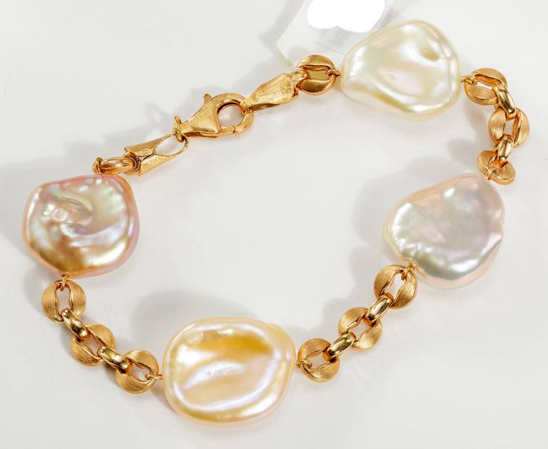 This Yvel chain bracelet features 4 freshwater Keshi pearls linked by 18k rose gold.  This bracelet measures 7 inches.