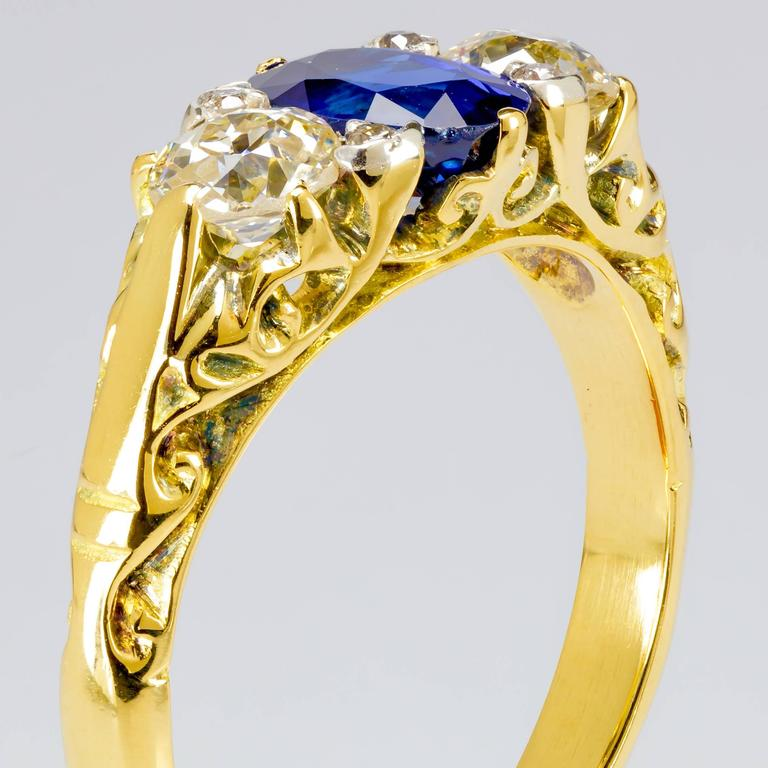 This one-of-a-kind 18k yellow gold ring features a 1.00 ct. oval sapphire measuring 7mmx5mm, 6 round brilliant diamonds totaling 0.60 ct., and intricate metalwork.    The ring measures a size 5.5.