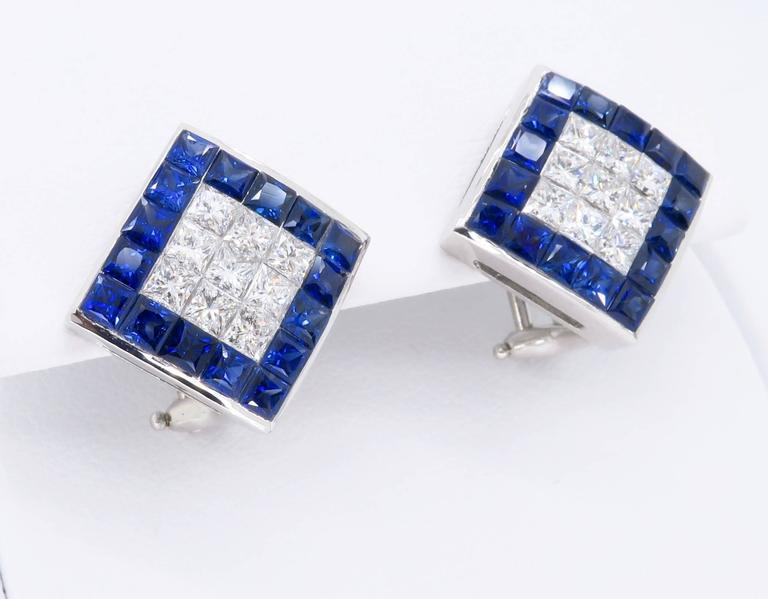 Gorgeous pair of 18K white gold diamond and sapphire earrings.  Each stunning earring houses 9 beautiful Princess Cut Diamonds and 16 blue lab created sapphires. The vivid blue sapphires surround approximately 1.44CTW of diamonds. The diamonds