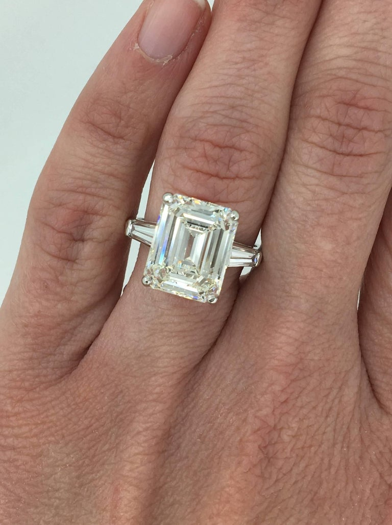 Classic ring features a stunning GIA Certified 6.21CT Emerald Cut Diamond in the center with J color and VS1 clarity. There are two tapered baguettes accenting the featured diamond. The platinum ring houses approximately 6.81CTW of diamonds. This