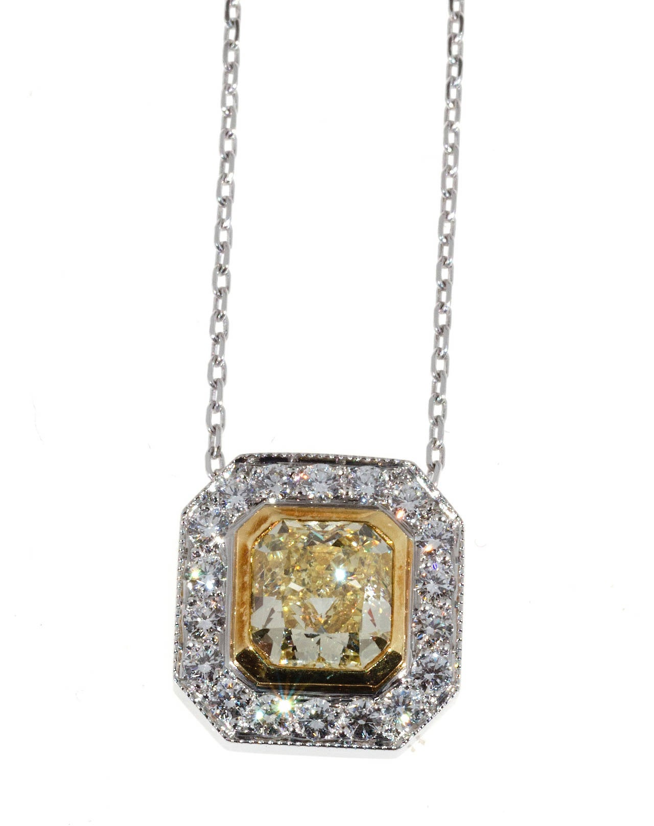 Radiant cut good fancy yellow canary diamond from an estate. Handmade platinum and 18k yellow gold setting from the Peter Suchy workshop. Pendant slides on chain. Extremely well cut. Very nice. ½ inch across.
