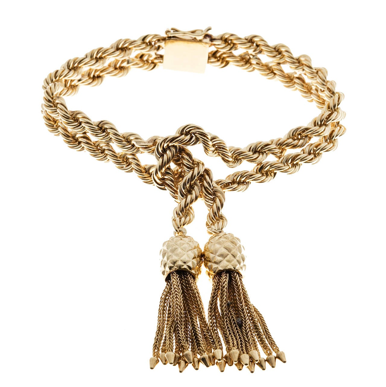 Classic Tiffany & Co solid rope bracelet with two rows of solid rope knotted in the center and holding two solid 3D tassels. One of the best we have seen.