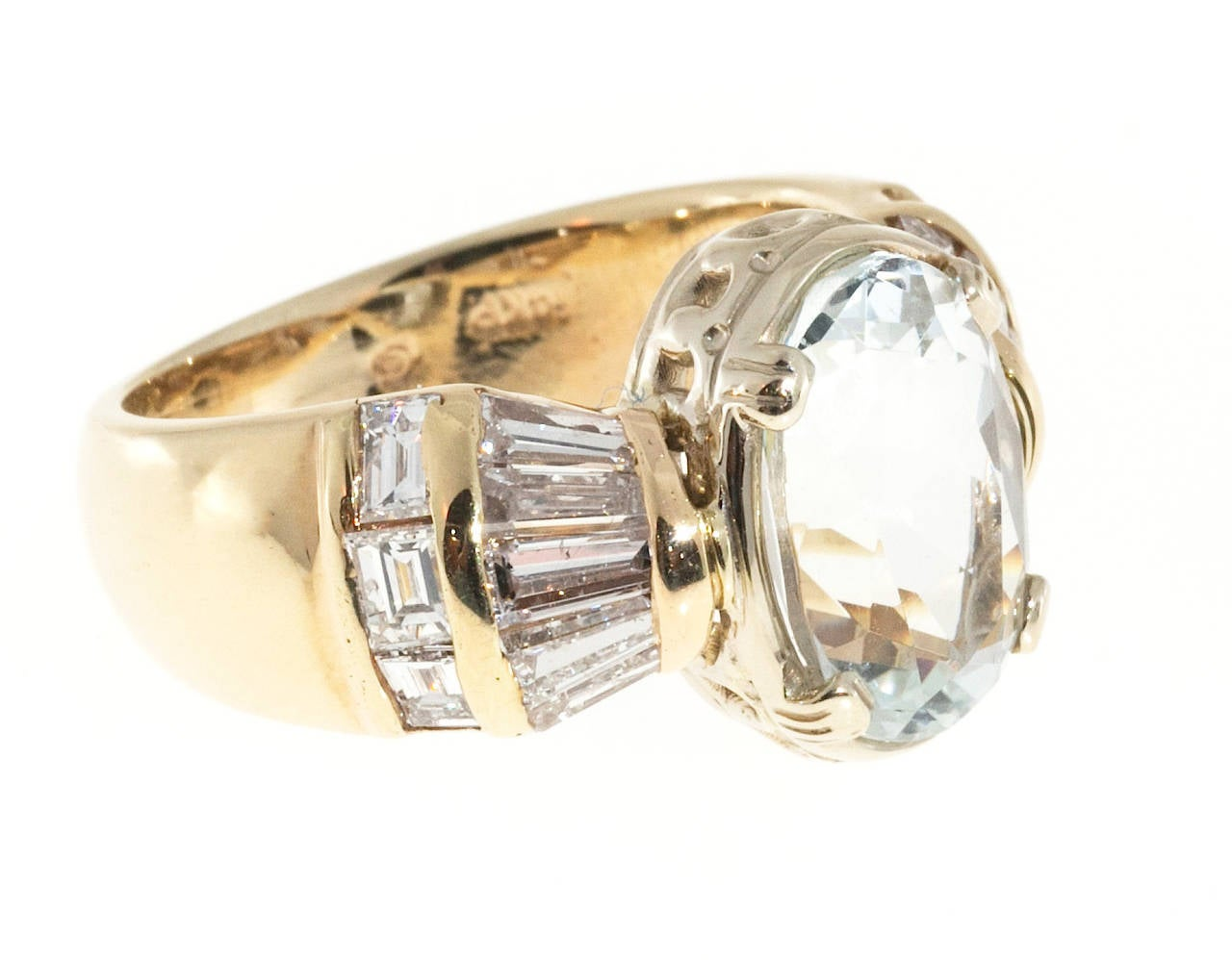 The center of this ring contains an aquamarine It is a  well cut clear Aquamarine, almost colorless and very bright. else. The stone is actually a very very pale blue. The  ring pulls all visual attention into the center stone. The shoulders of the