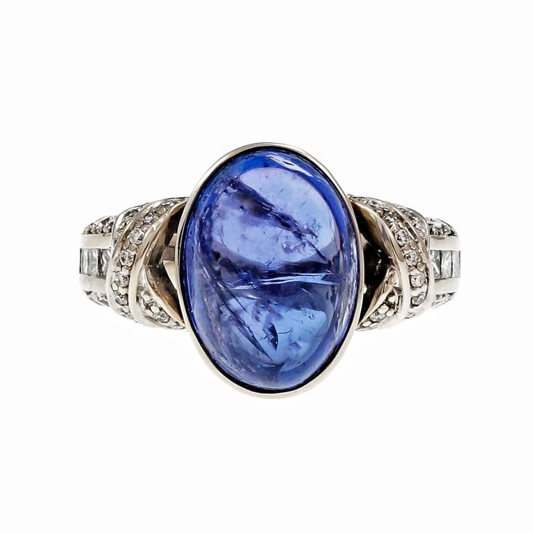 "Bright blue oval cabochon Tanzanite engagement ring with excellent translucent glow. 1970-1980. White gold diamond set ""X"" design ring.  1 oval cabochon bluish purple Tanzanite, approx. total weight 9.88cts, MI 8 Princess cut diamonds, approx. total"