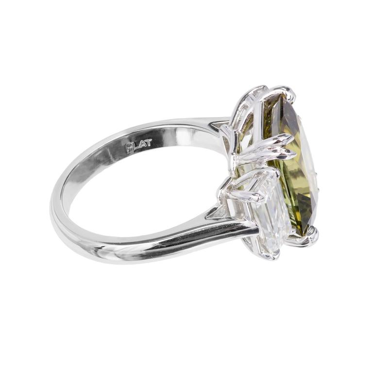 Peter Suchy emerald step-cut 7.68ct natural alexandrite engagement ring with D color emerald-cut diamonds. The stones are all GIA certified. The alexandrite has moderate to fair color change from yellow green to brown green. The setting is brand new
