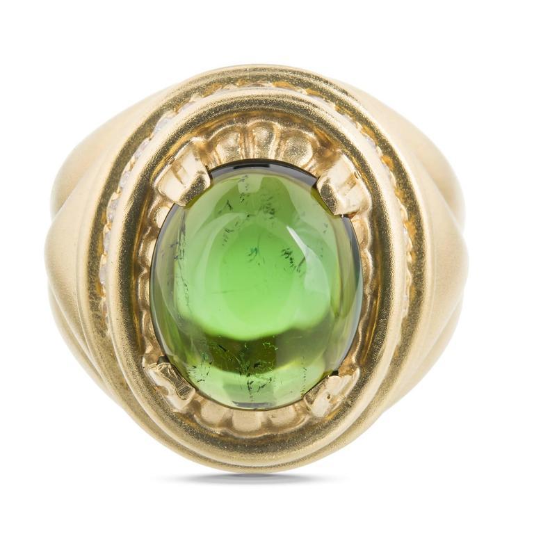 Matt finish textured yellow ring set with a bright green Tourmaline cabochon and full cut Diamonds.  1 oval green cabochon Tourmaline, approx. total weight 4.50ts, SI, 12.9 x 10.9mm 44 full cut diamond approx. total weight .40cts, G, VS 18k yellow
