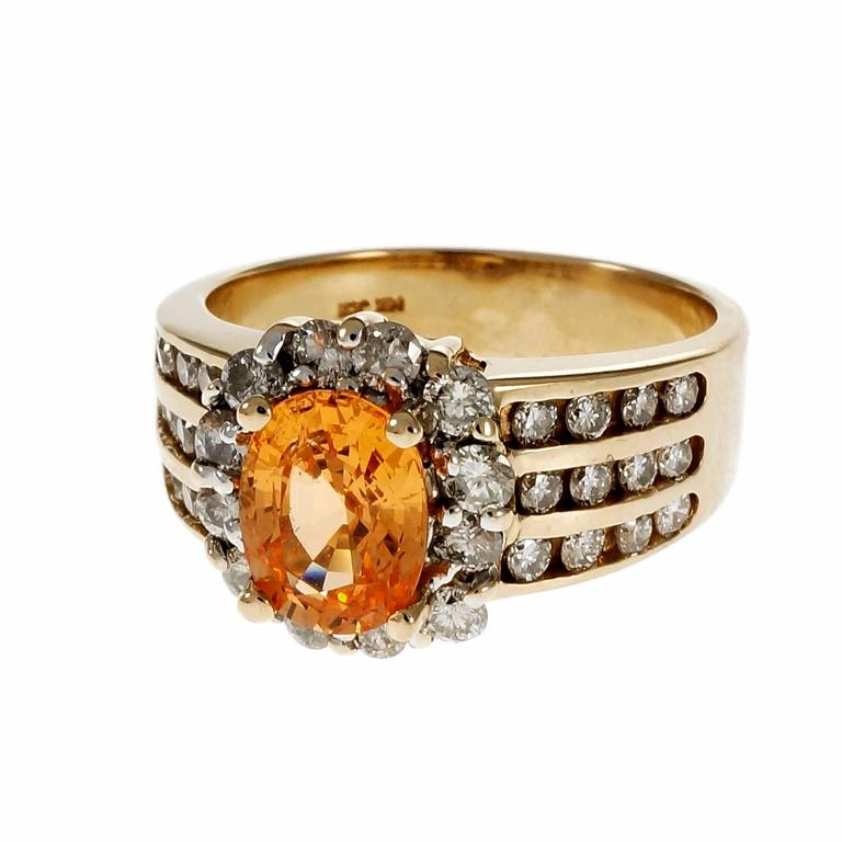 Estate bright orange Spessartite Garnet with a diamond halo and three rows of Diamonds on each side in a 14k yellow gold setting.   1 oval Spessartite orange Garnet, approx. total weight 1.81cts, VS 36 round full cut Diamonds, approx. total weight