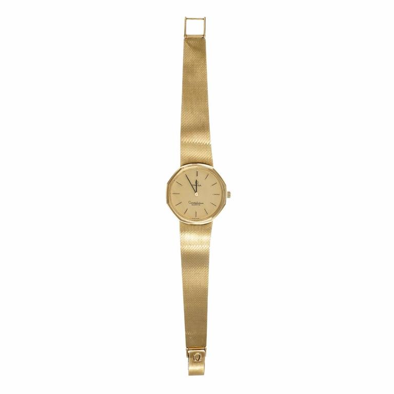 Omega Constellation Quartz wrist watch. 14k gold with Omega 14k mesh band.  14k yellow gold 67.5 grams Band length: 7.5 – 7.75 inches Length: 33mm Width: 33mm Band width at case: 18mm Case thickness: 7.4mm Band: 14k Omega 1291/253 Crystal: