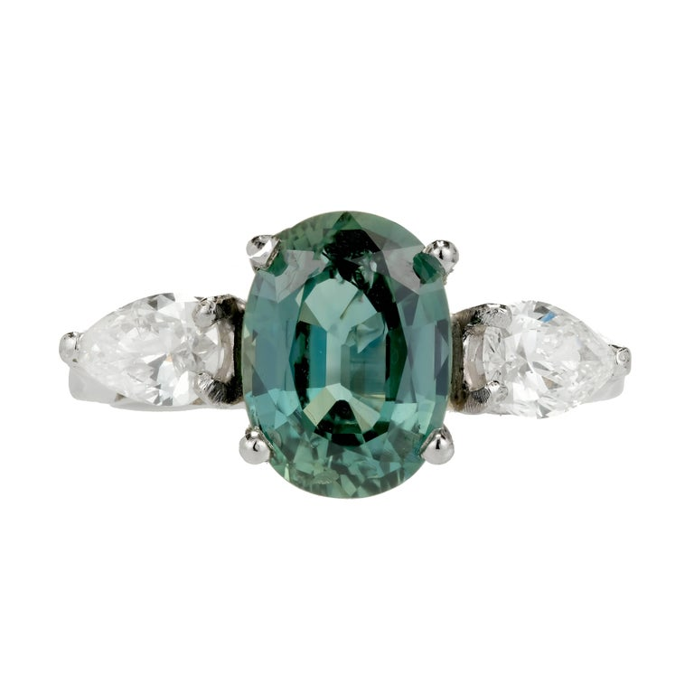Green Sapphire Diamond Platinum engagement ring. The center stone is a bright bluish green oval with an incredible presence. Flanked by 2 pear shaped bright white Diamonds. circa 1960-1970. Certified by the GIA as natural green Sapphire, no heat and