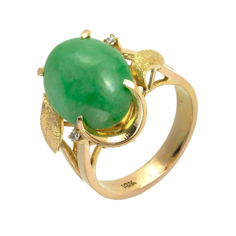 Natural Jadeite Jade mottled green ring in 18k yellow gold with shiny Diamond accents and hand textured gold leaves.  1 oval cabochon mottled green Jadeite Jade, 16.47 x 11.45 x 3.96mm, GIA certificate #2185636049 2 single cut Diamonds, approx.
