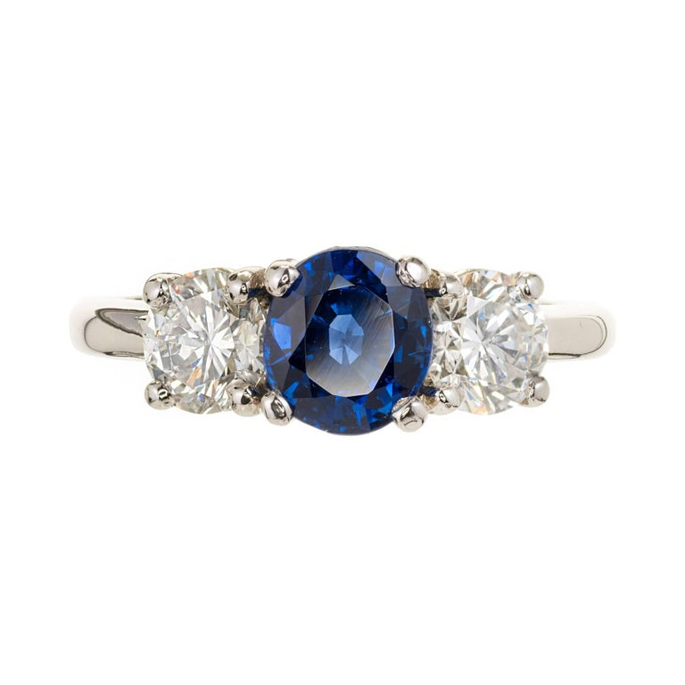 Classic three-stone ring with blue Sapphire center and 2 side diamonds. GIA certified Sapphire, fine Royal blue, simple heat only. Bright white well cut diamond sides. Peter Suchy Designs ring.   950 Platinum 1 oval blue Sapphire, approx. total